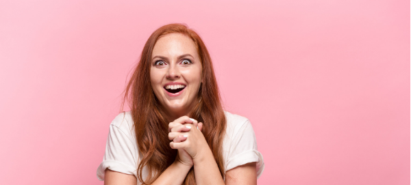 Woman looking happy and excited, pink background