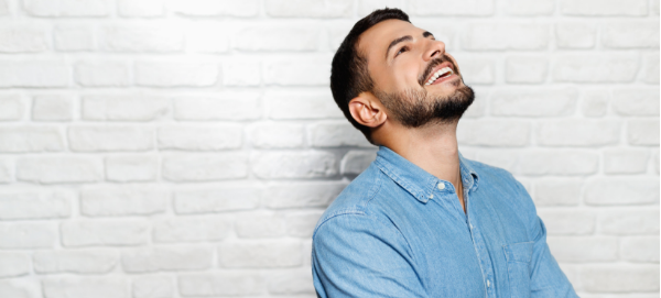 Young bearded businessman looking up and laughing, optimistic