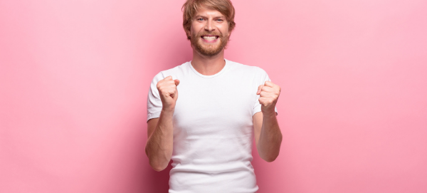 Bearded young man excited and thrilled with fists upraised, pink background