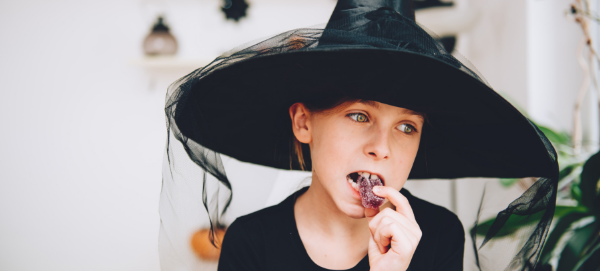 Young child dressed in Halloween costume eating candy
